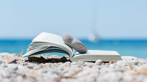 book on the beach with a rock keeping it open