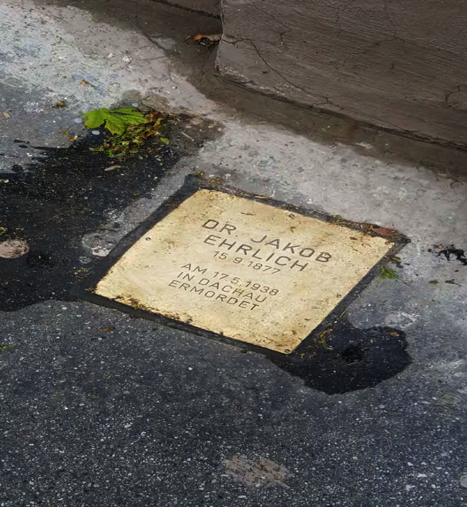 "A Stolpersteine (""stumblestone"") plaque outside the building to honor a former inhabitant of the building who had been deported to Dachau and murdered in April 1938."